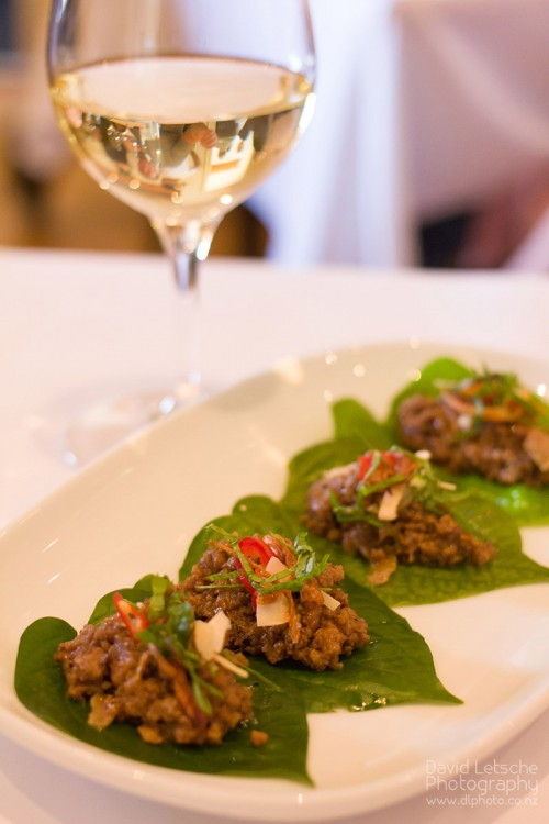 Fresh betel leaves with sticky caramelised pork with incendiary components